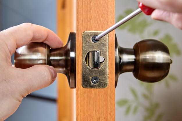 Montaż nowych mosiężnych klamek z zatrzaskiem w drewnianych drzwiach wewnętrznych, ręka ślusarza ze śrubokrętem.
