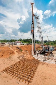 Montaż pali nowego fundamentu w domu w trakcie budowy