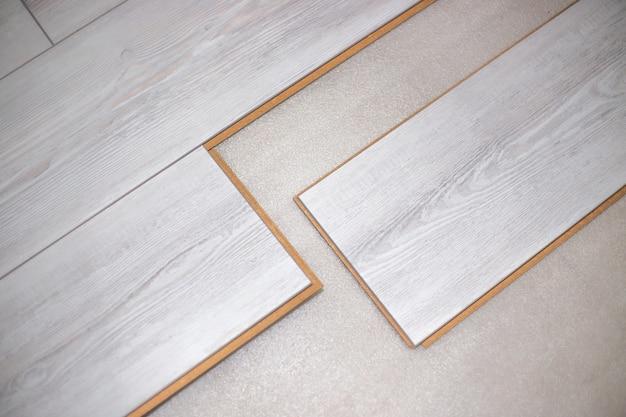 Montaż paneli podłogowych z jasnego drewna w pomieszczeniu mieszkalnym. remont domu i biura oraz