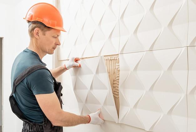 Montaż panelu gipsowego 3d. pracownik mocuje płytkę gipsową do ściany.