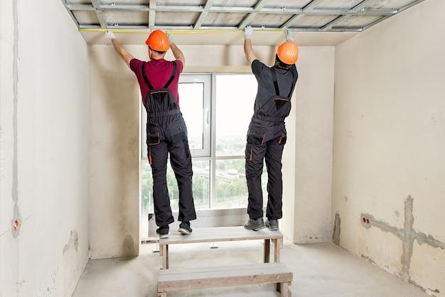 Montaż płyt kartonowo-gipsowych. pracownicy mierzą sufit.