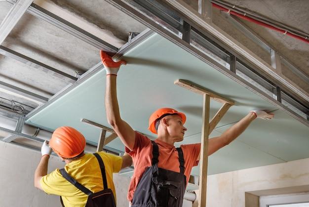 Montaż płyt kartonowo-gipsowych. pracownicy mocują płytę gipsowo-kartonową do sufitu.