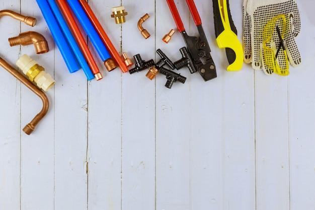Montaż rur plastikowych do instalacji wodnej, narzędzi do cięcia rur, narożników, uchwytów, kurków, adapterów i rękawic roboczych na sprzęcie hydraulicznym na placu budowy
