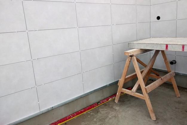 Montaż ściennych płytek ceramicznych na kleju do zaprawy.