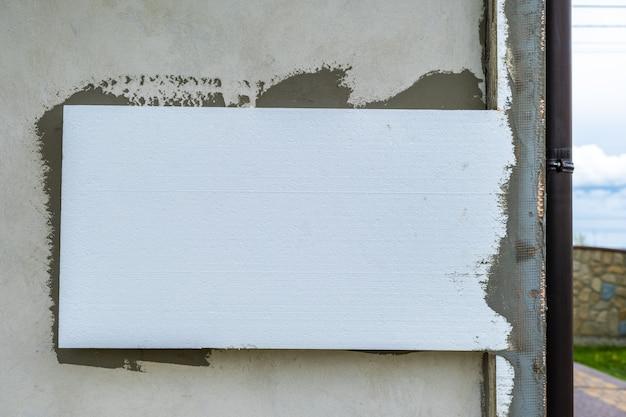 Montaż styropianowych płyt izolacyjnych na elewacji domu w celu ochrony termicznej.