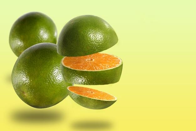 Montaż z trzech owoców pomarańczy, jednego ciętego i dwóch całych, z żółtym tłem.
