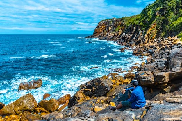 Monte ulia w mieście san sebastián, kraj basków. odwiedź ukrytą zatokę miasta o nazwie illurgita senadia lub illurgita senotia. młody mężczyzna w niebieskiej kurtce, ciesząc się morzem