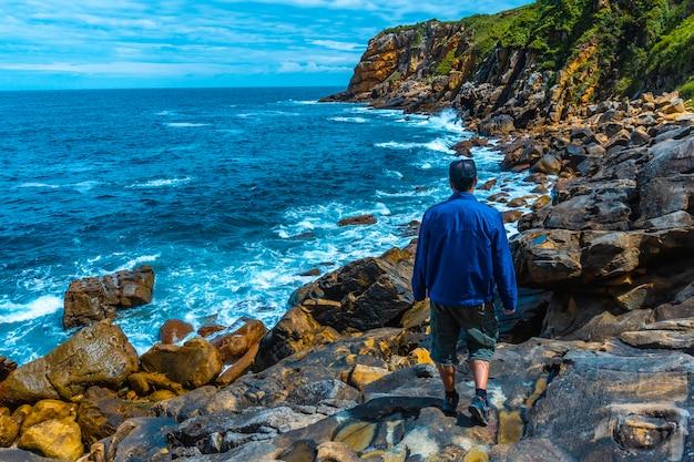 Monte ulia w mieście san sebastián, kraj basków. odwiedź ukrytą zatokę miasta o nazwie illurgita senadia lub illurgita senotia. młody mężczyzna w niebieskiej kurtce nad morzem