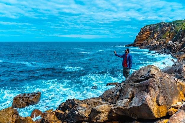 Monte ulia w mieście san sebastián, kraj basków. odwiedź ukrytą zatokę miasta o nazwie illurgita senadia lub illurgita senotia. młody mężczyzna w niebieskiej kurtce w zatoczce robi zdjęcie