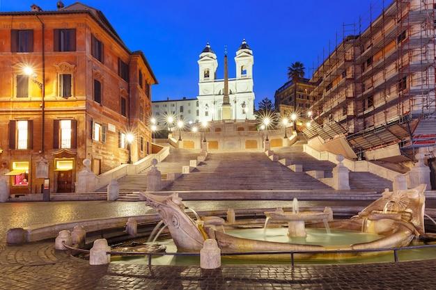 Monumentalne schody hiszpańskie schody, widziane z piazza di spagna, i wczesnobarokowa fontanna zwana fontana della barcaccia lub fontanna brzydkiej łodzi podczas porannej niebieskiej godziny, rzym, włochy.