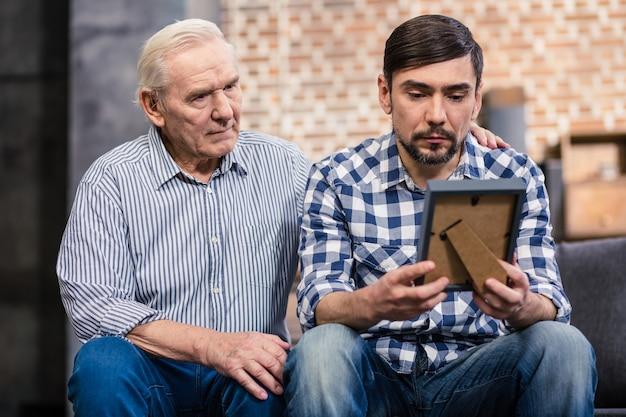 Moody mężczyzna trzymający ramkę na zdjęcia, podczas gdy jego emerytowany ojciec go wspiera