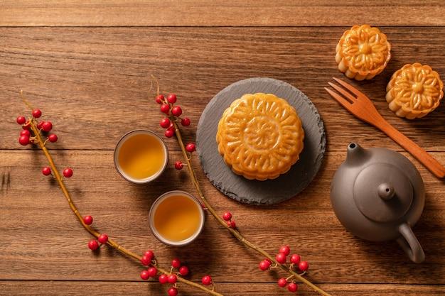 Moon cake mooncake ustawienie stołu - chińskie tradycyjne ciasto z filiżankami herbaty na drewnianym tle, koncepcja mid-autumn festival, widok z góry, płasko leżał