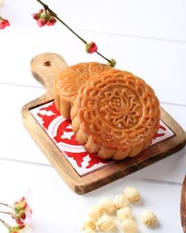 Mooncake na jasnoróżowym tle z różowym kwiatem. concept moon cake na święto środka jesieni lub chiński nowy rok (imlek). mooncake popularny jako kue bulan.