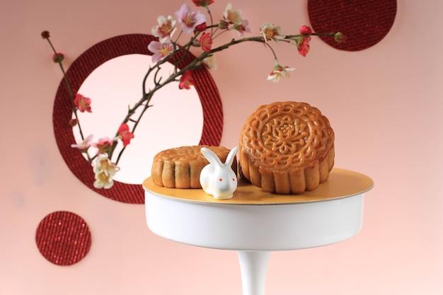 Mooncake na jasnoróżowym tle z różowym kwiatem. koncepcja moon cake na święto środka jesieni. mooncake popularny jako kue bulan.