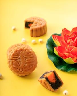 Mooncake na jasnożółtym tle z pomarańczowym kwiatem lotosu. koncepcja moon cake na święto środka jesieni. mooncake popularny jako kue bulan.