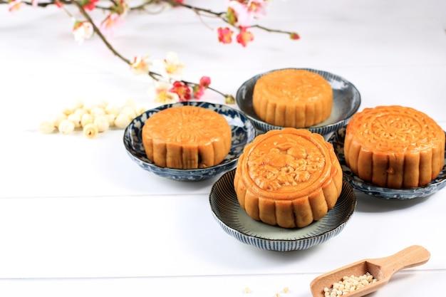 Mooncake na jasnym tle z herbatą. concept moon cake na święto środka jesieni lub chiński nowy rok (imlek). mooncake popularny jako kue bulan. podawane z chińską herbatą, kopiowanie miejsca na tekst