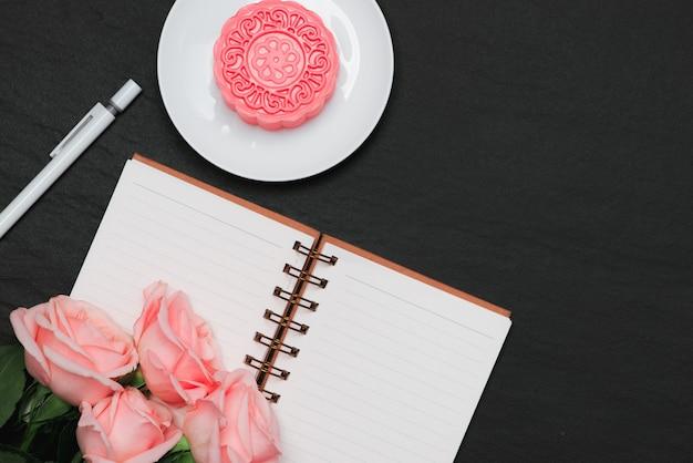Mooncake ze śnieżnej skóry i różowe kwiaty. otwórz notatnik z miejscem na kopię.