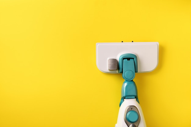 Mop do czyszczenia parą na żółtym tle.