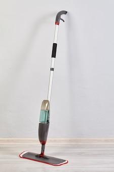 Mop do czyszczenia podłogi ściereczką z mikrofibry i pojemnik na środek czyszczący stoi.