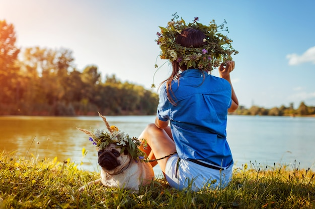 Mops pies i jego pan chłodzi nad rzeką, nosząc wieńce kwiatowe. szczęśliwy szczeniak i kobieta cieszy się lato naturę outdoors