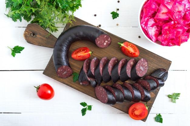 Morcilla - kiełbasa z krwi. kawałki hiszpańskiego czarnego puddingu na drewnianej desce do krojenia na białym stole.