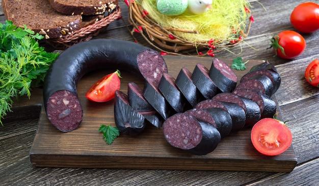 Morcilla - kiełbasa z krwi. kawałki hiszpańskiego czarnego puddingu na drewnianej desce do krojenia.