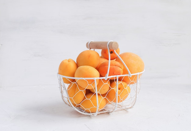 Morele i brzoskwinie w metalowym koszu owoce letnie zbiór owoców ekologicznych biały