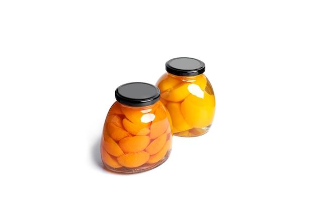 Morele i brzoskwinie w puszkach w szklanym słoju. słodkie morele i brzoskwinie w syropie na białym tle.