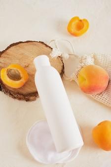 Morele i makieta plastikowej białej butelki na krem lub mydło, drewniane podium z cięcia piłą wykonanego z drewna na jasnym tle widok z góry