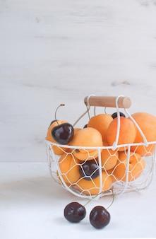 Morele i wiśnie w metalowym koszu letnie owoce i jagody zbiór owoców ekologicznych biały
