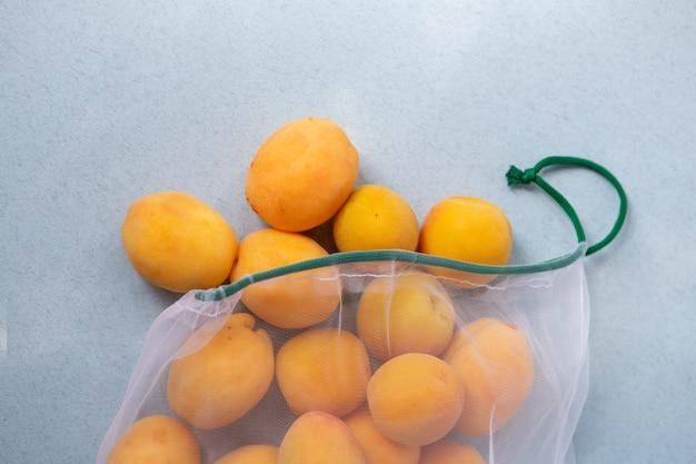 Morele w ekologicznym opakowaniu. torby wielokrotnego użytku na warzywa i owoce. zakupy w sklepie, sprzedaż detaliczna. ekologiczne opakowanie.