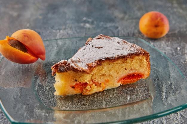 Morelowe migdałowe ciasto z wyciętym kawałkiem na szklanej płytce na betonowym tle.