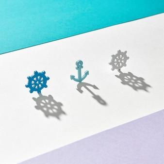 Morski wzór z kotwicy i kół z długimi, twardymi cieniami na trójkolorowym kolorze z miejscem na kopię.