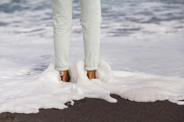 Morskie fale z białą delikatną pianą spływającą po kobiecych stopach w jasnoniebieskich dżinsach. kobiece stopy na piasku na plaży.