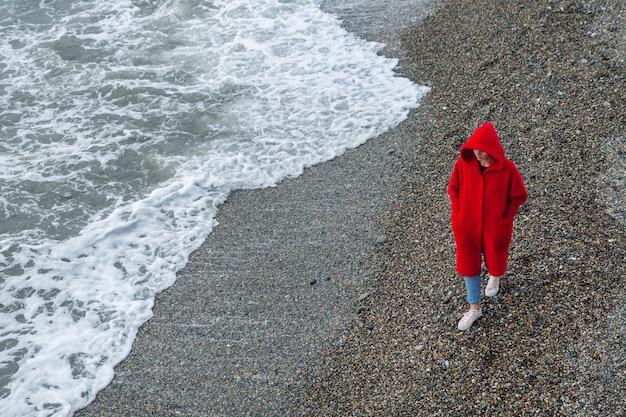 Morskie fale, żwirowy brzeg. kobieta w czerwonym płaszczu z kapturem spaceruje po plaży, zimowy dzień.