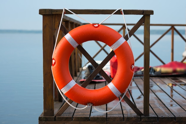 Morskie koło ratunkowe na ogrodzeniu na powierzchni wody