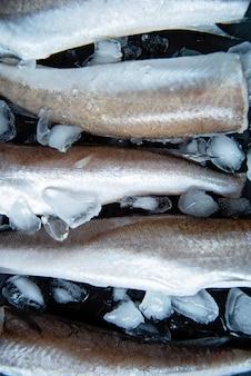 Morszczuk z surowej ryby. pięć filetów z surowej ryby na lodzie w ciemności,