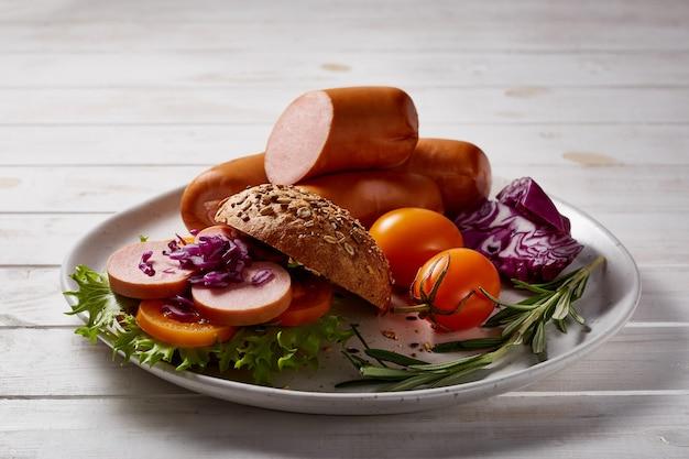 Mortadela z warzywami i ziołami na drewnianym talerzu na drewnianym stole.
