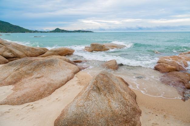 Morza i skał kamienie na plaży z piaska i niebieskiego nieba tłem