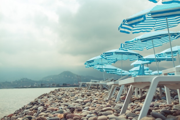 Morze czarne i żwirowa plaża z parasolami i leżakami na tle gór. urlop na morzu i relaksujący czas