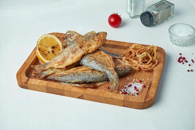 Morze czarne smażone ryby panierowane na drewnianej desce na białym stole. ścieśniać