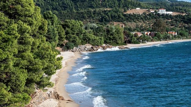Morze egejskie wybrzeże grecji, skaliste wzgórza porośnięte drzewami i krzewami, plaża z falami, zabudowania położone blisko wybrzeża