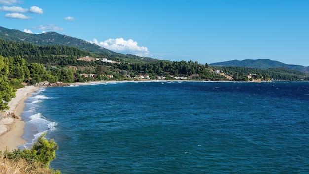 Morze egejskie wybrzeże grecji, skaliste wzgórza porośnięte drzewami i krzewami, zabudowania położone blisko wybrzeża