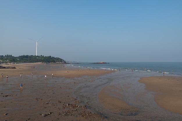Morze, fale, wyspy i plaże o zmierzchu.