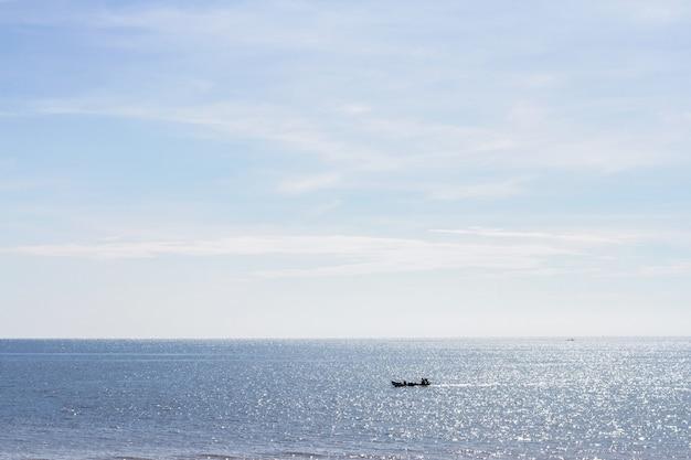 Morze i plaża z łodzią rybacką na letni poranek
