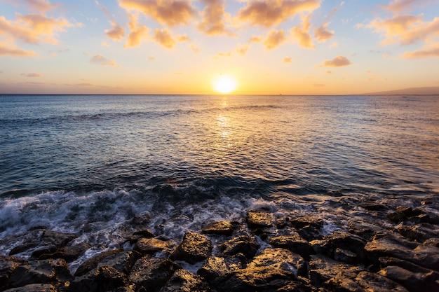 Morze i skała o zachodzie słońca