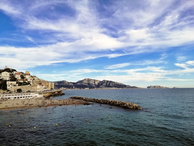 Morze otoczone budynkami i wzgórzami pod zachmurzonym niebem i światłem słonecznym w marsylii we francji