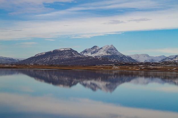 Morze otoczone przez skaliste góry pokryte śniegiem i odbijające się w wodzie na islandii