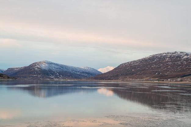 Morze otoczone skałami pokrytymi śniegiem i odbijające się w wodzie na islandii