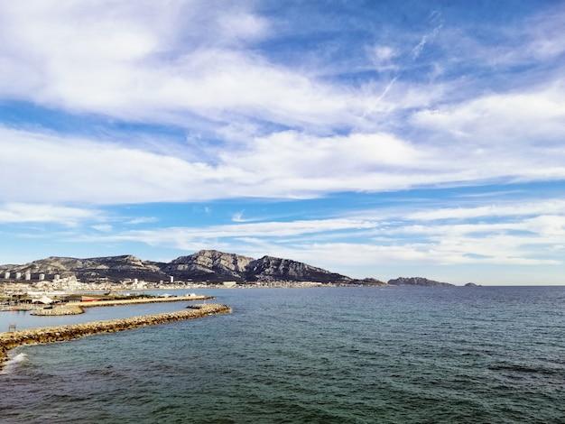 Morze otoczone skałami w słońcu i zachmurzone niebo w marsylii we francji
